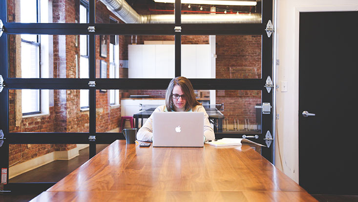Ein Student sitzt an einem Tisch und sieht auf den Bildschirm eines Laptops