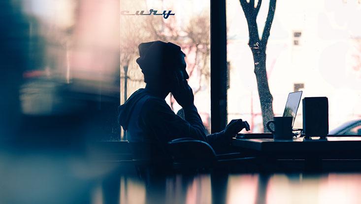 Das Bild zeigt einen jungen Mann im Dämmerlicht vor einem Laptop sitzend