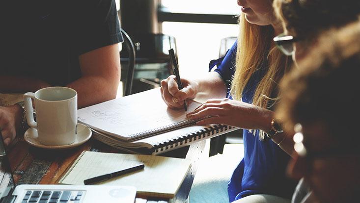 Studierende beim Schreiben und im Austausch