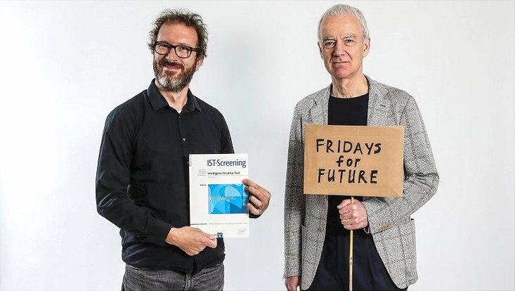 Prof. Jan Wacker (l.) mit einem Intelligenztest, Prof. Hans-Christoph Koller mit einem Protestschild.