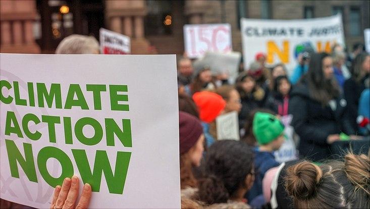 """Auf einer Demonstration wird das Plakat """"Climate Actio Now"""" hoch gehalten."""