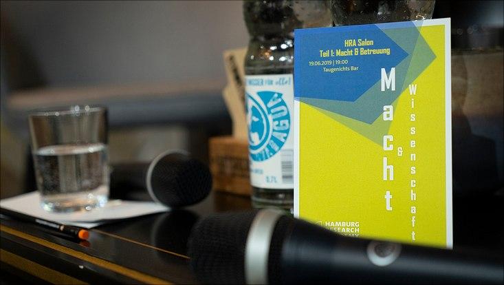 """Auf einem Tisch liegen zwei Mikrofone und ein Flyer des HRA Salons zum Thema """"Macht und Wissenschaft""""."""