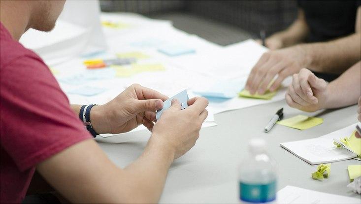Mehrere Personen sitzen an einem Tisch. Der Fokus liegt auf deren Hände, die in der Tischmitte mit Klebezetteln arbeiten.