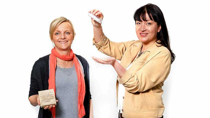 """Helena Herr (l.) zeigt einen beschrifteten """"Holzdrifter"""" aus einer Versuchsreihe von Wissenschaftlern der Uni Oldenburg zum Meeresmüll. Elke Fischer hat ein Röhrchen mit Mikroplastik mitgebracht."""