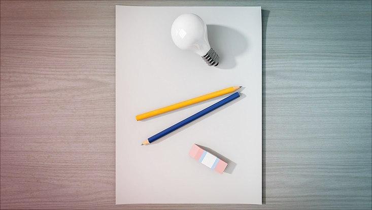 Ein leeres Blatt Papier, eine Glühbirne, zwei Bleistifte sowie ein Radiergummi liegen auf einem Tisch.