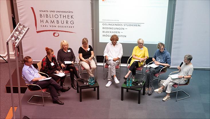 Verschiedene Podiumssprechende sitzen im Stuhlkreis auf einer Bühne