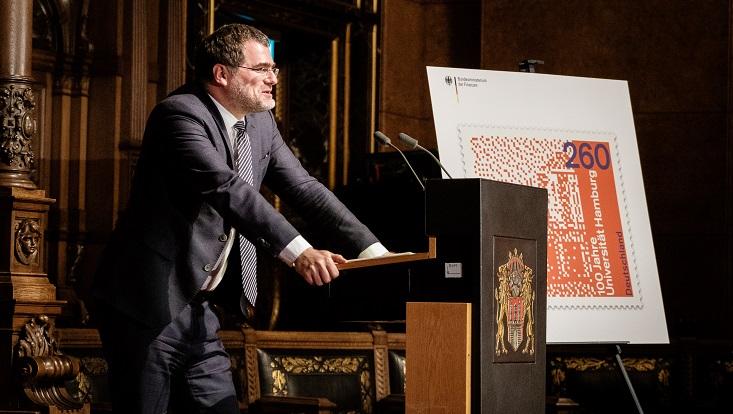 Staatssekretär Wolfgang Schmidt (Bundesministerium für Finanzen) steht an einem Rednerpult im Großen Festsaal des Rathauses. Rechts daneben ist eine Staffelei mit der übergroßen Reproduktion der Sonderbriefmarke.