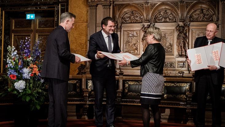 Staatssekretär Schmidt überreicht ein rotes Album mit der Sonderbriefmarke an Frau Duden, Vizepräsidentin der Bürgerschaft. Rechts im Bild steht Präsident Lenzen und hält ein geöffnetes Album in den Händen.