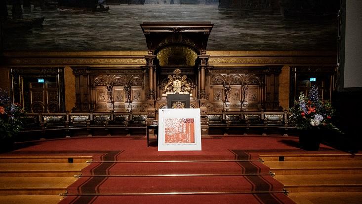 Das Foto zeigt die übergroße Reproduktion der Sonderbriefmarke, die vorne gegen das Rednerpult gelehnt ist.