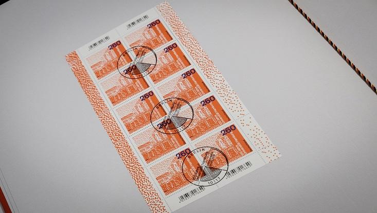 Das Foto zeigt einen gestempelten Bogen der Sondermarke mit dem Wert 2,60 EURO. Auf der in Rot gehaltenen Briefmarke ist der linke Teil des Hauptgebäudes zu sehen, in einer gepunkteten Darstellung, die vielleicht an einen QR-Code erinnern soll.