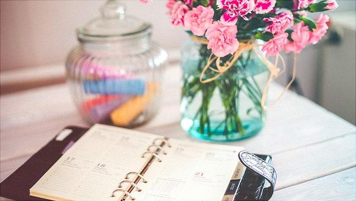 Ein aufgeschlagener Kalender liegt auf einem Tisch, im Hintergrund Blumen