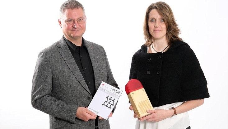 Prof. Dr. Sven Degenhardt trägt ein barrierefreies Türschild aus der Universität Hamburg, Prof. Dr. Annika Herrmann ein Lichtsignal für Gehörlose.