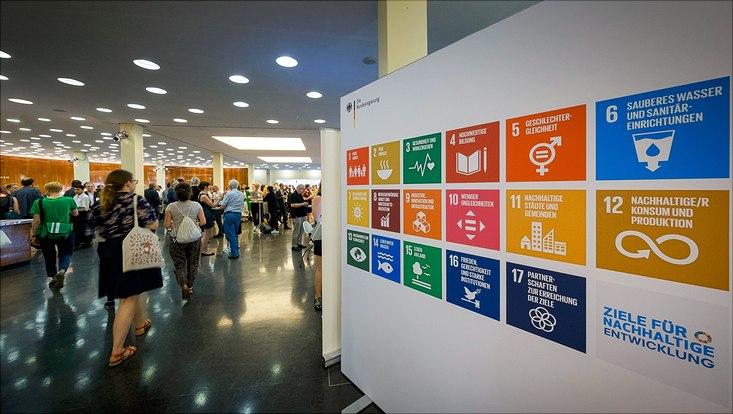 Konferenz. Auf der linken Seite laufen Menschen. Auf der rechten Seite ist ein Plakt mit den 17 Sustainable Development Goals.
