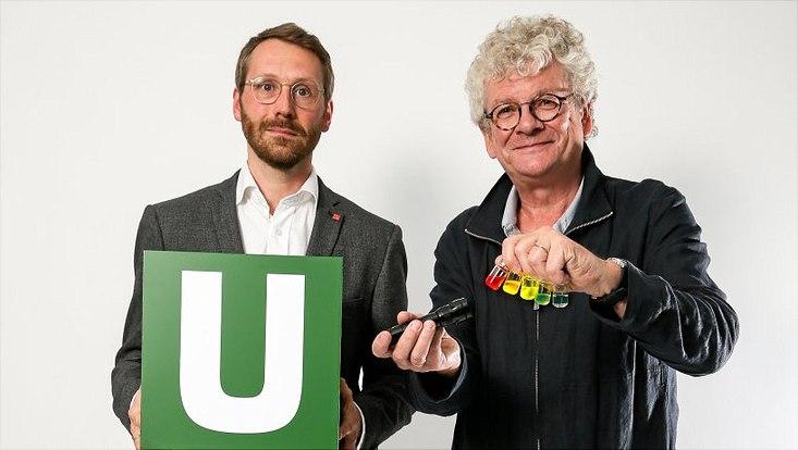 """Marc Fabian Buck (l.) hält ein grünes """"U"""", neben ihm steht Horst Weller und hält in der einen Hand fünf kleine Galsbehälter mit bunten Flüssigkeiten, in der anderen eine Taschenlampe"""