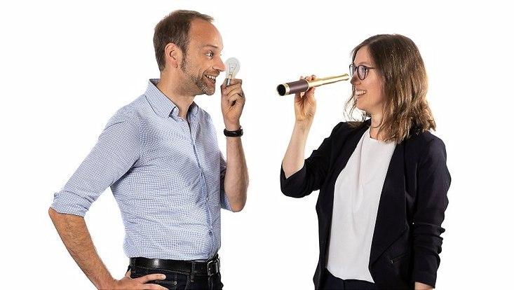 Prof. Jan Marcus hält eine Gühbirne und steht neben Prof. Julia Gerick die ein kleines Fernrohr hält. Beide blicken sich an.