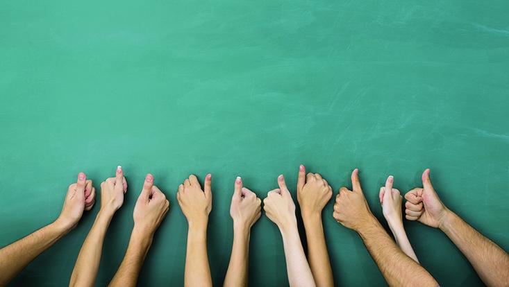 Aufzeigende Hände vor Tafel