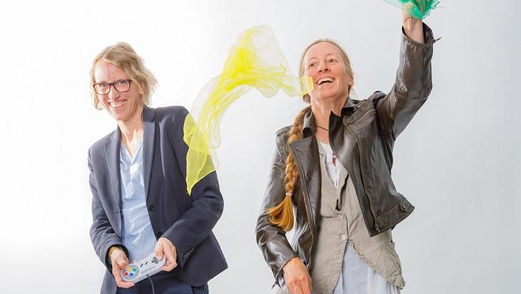 Prof. Kathrin Fahlenbach mit einem Joystick in den Händen und Prof. Ingrid Bähr, die Tücher in die Luft wirft