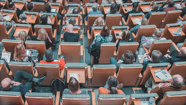 People sitting in chairs in a lecture hall or conference room. View from above.