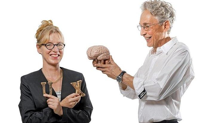 """Prof. Anke Grotlüschen hält ein """"U"""" und ein """"X"""" in den Händen und Prof. Dietmar Kuhl hält ein Gehirnmodell"""