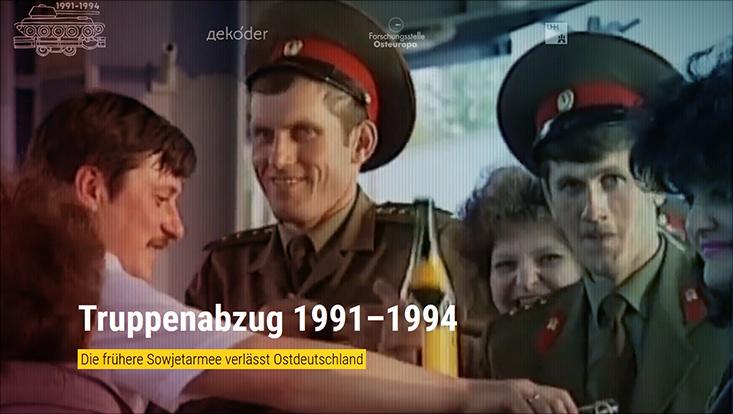 Das Bild zeigt eine Gruppe fröhlicher sowjetischer Soldaten beim Abschied aus Ostdeutschland auf einem Bahnhof.