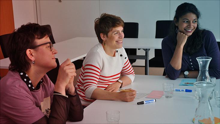 Das Bild zeigt Mitarbeitende des Universitätskollegs beim Gespräch.