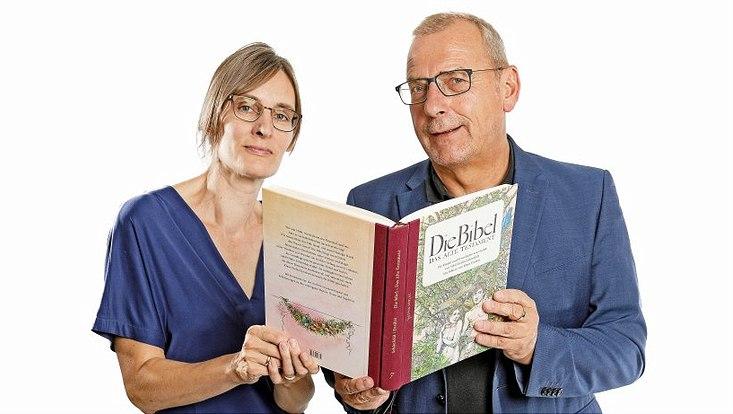 Prof. Dr. Christine Büchner und Prof. Dr. Sighard Neckel halten eine illustrierte Fassung des Alten Testaments zusammen in den Händen