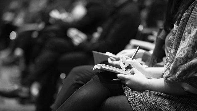 Das Bild zeigt eine sitzende Frau in einer Reihe von Tagungsteilnehmenden, die auf ihren Knien ein Notizbuch liegen hat, in dem sie Gehörtes mitschreibt.