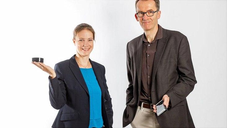 Alexa Burmester hält einen Sprachassistenten in der Hand und Uwe Hasebrink hält ein Smartphone