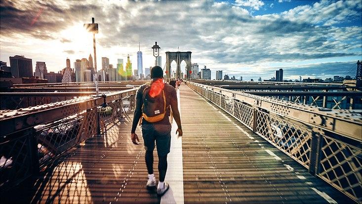 Mann läuft über Brooklyn Bridge Richtung Manhattan
