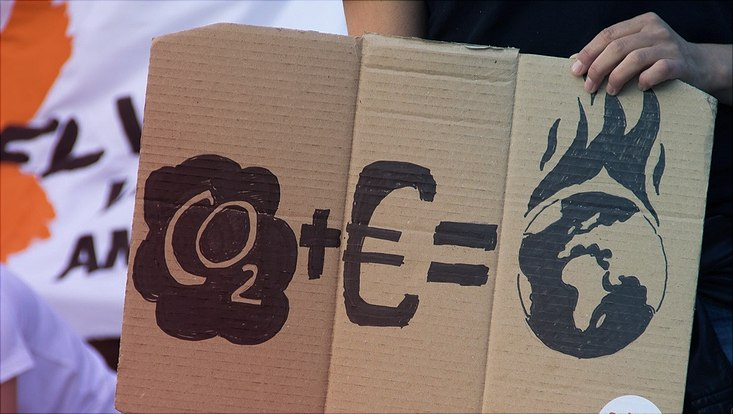 Ein Plakat auf einer Demonstration zeigt grafisch die Formel: CO2 + Eurozeichen = Erdball in Flammen.