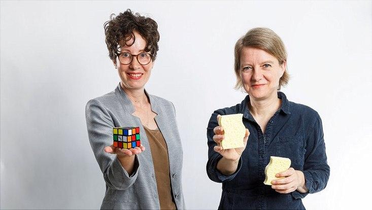 Dr. Lisa Knoll (l.) hält einen Zauberwürfel in der Hand. Dr. Stefanie Mallon hält in jeder Hand einen Schwamm.