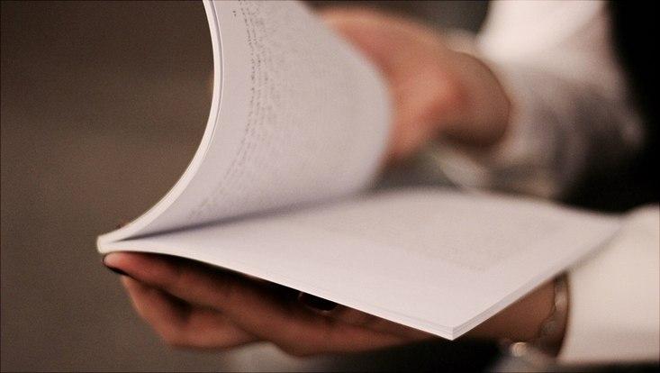 Hände öffnen gerade eine Publikation/Buch/Heft