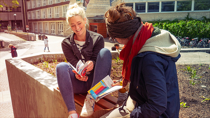 Das Bild zeigt zwei Studentinnen auf dem UHH-Campus bei der Lektüre des UK-KVV