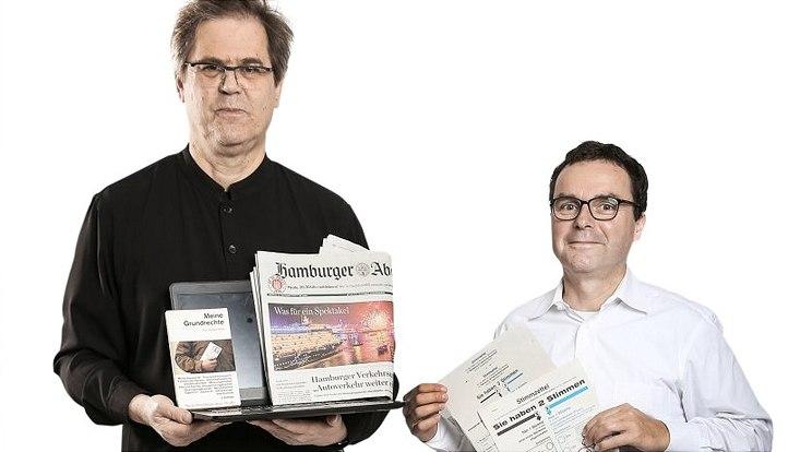 Professor Tilman Grammes hält einen Laptop, eine Zeitung und ein Buch in den Händen und Professor Kai-Uwe Schnapp hält Stimmzettel in den Händen.