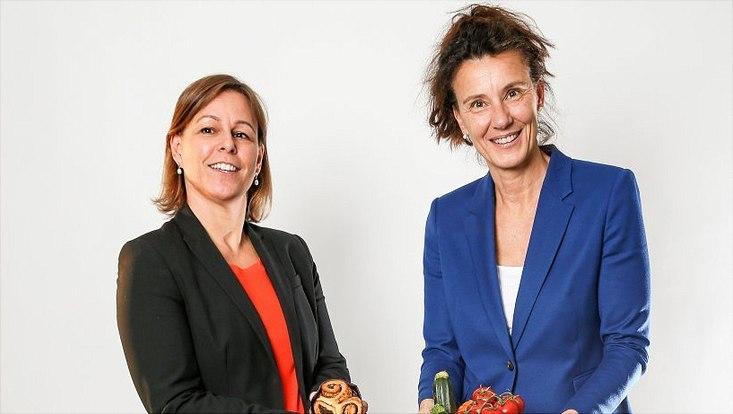 Anne-Katharina Fladung hält Süßgebäck in der Hand und Birgit-Christiane Zyriax hält Tomaten und Zucchini.