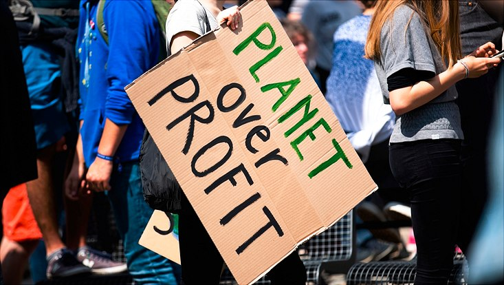 "Protest sign saying ""Planet over Profit"""