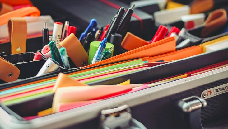 Inhalt eines Methodenkoffers. Viele Stifte, buntes Papier und Post-It Notes