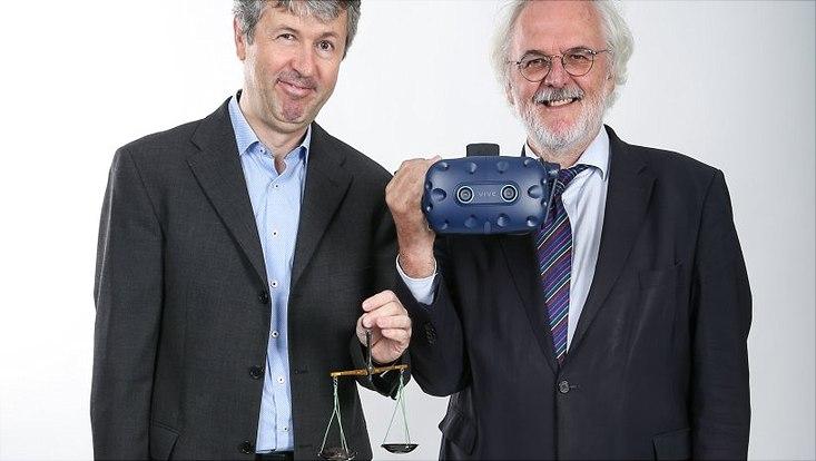 Prof. Mathias Kifmann (l.) hält eine Waage und Prof. Burkhard Göke eine Brille für virtuelle Realität.