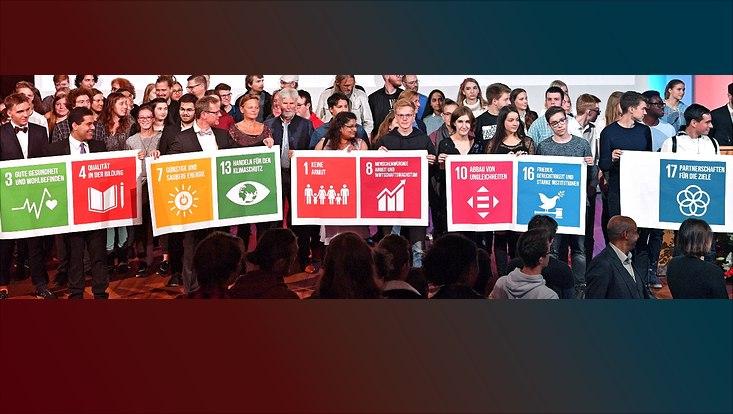 Studierende halten während der Immatrikulationsfeier SDG-Symbole hoch