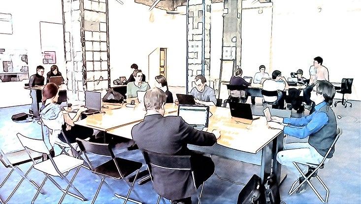 Menschen sitzen an Tischen mit Computern und arbeiten zusammen.