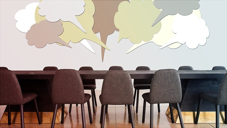 Stühle vor einem Tisch über dem grafisch dargestellte Sprechblasen schweben