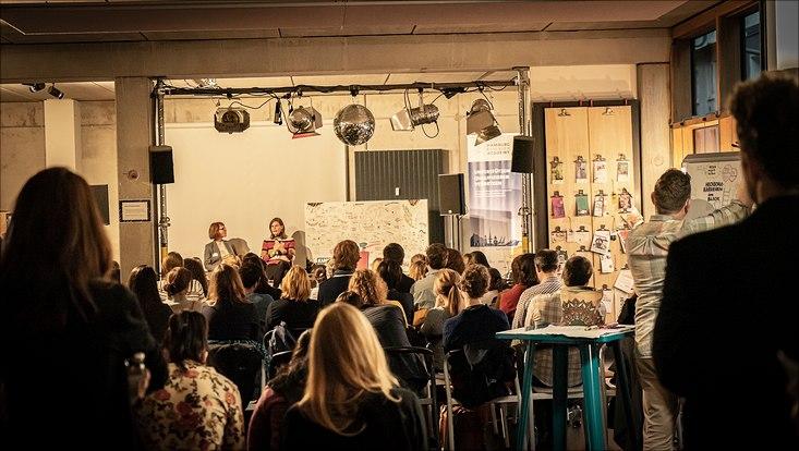 Die Teilnehmende sitzen vor einer kleinen Bühne, auf der ein Karrieretalk mit Dr. Muriel Helbig, Präsidentin der TH Lübeck, stattfindet.
