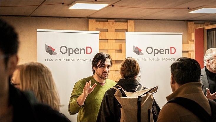Teilnehmende stehen vor einem Infostand der Firma Open D.