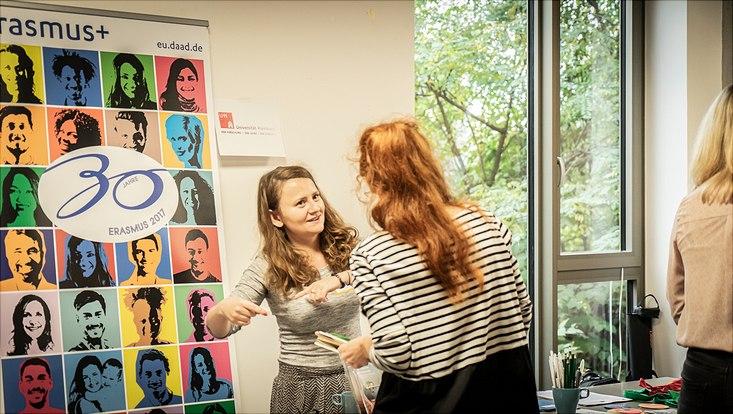 Eine Teilnehmerin steht an einem Infostand von Erasmus+.