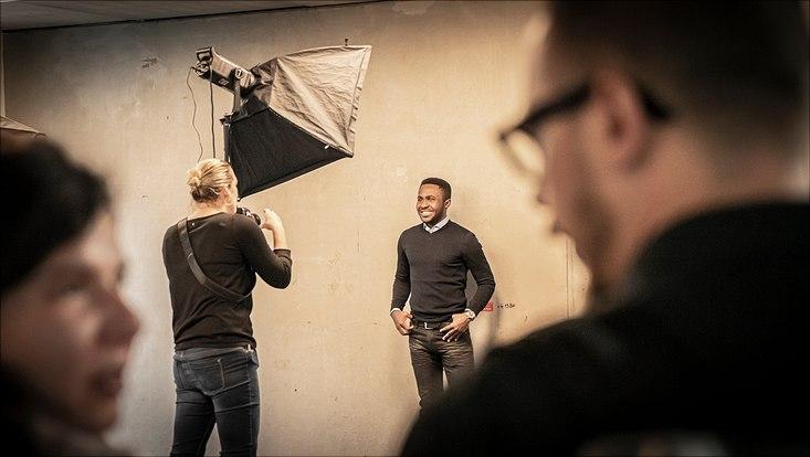 Eine Fotografin macht Bewerbungsfotos von den Teilnehmenden.