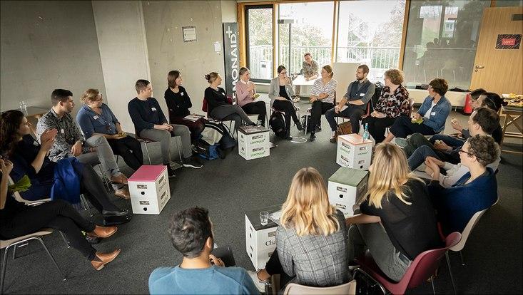 Teilnehmende sitzen in einem Stuhlkreis und diskutieren.