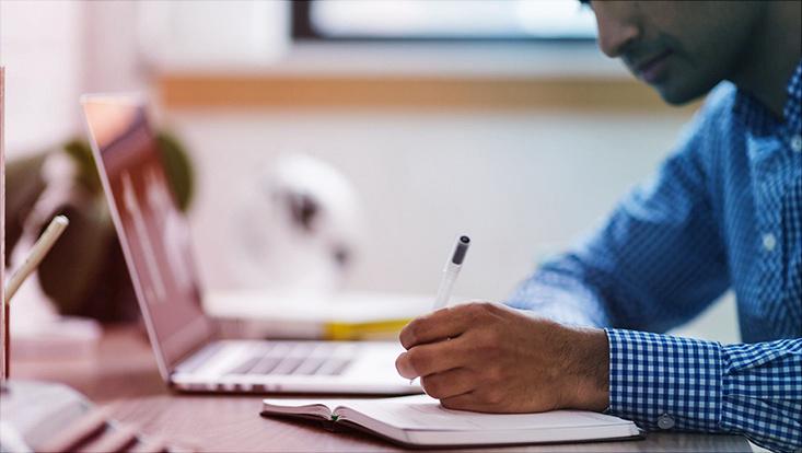 Das Bild zeigt einen jungen Mann vor einem Laptop beim Schreiben mit der Hand in einem Notizbuch.