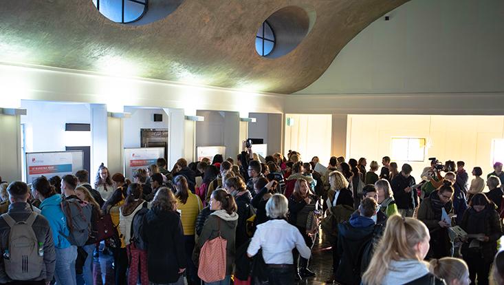 Eine große Menge an Schülerinnen und Schüler im Hörsaal vor Plakaten