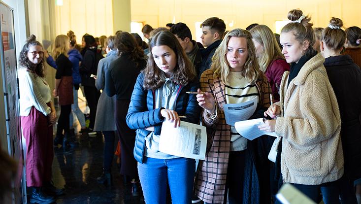 Schülerinnen schauen sich ein Plakat an, überlegend mit Aufgabenzetteln in ihren Händen