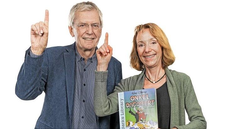 Prof. Rolf von Lüde und Prof. Ingrid Größl. heben jeweils dem linken Zeigefinger in die Höhe. Frau Größl hält ein Onkel Dagobert Comic in der anderen Hand.